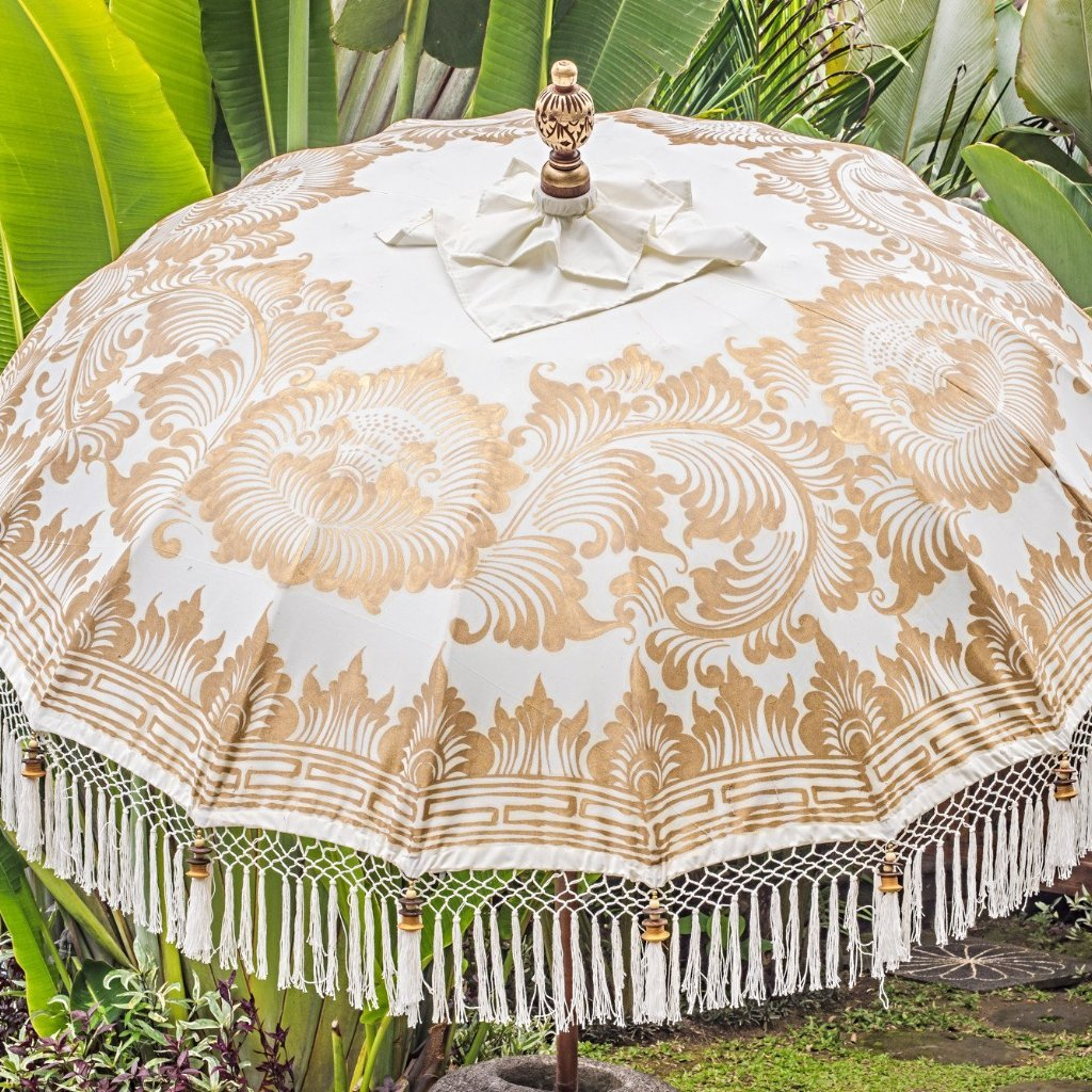 Big Simone- Cream white and gold garden handmade bali parasol with fringing pom poms and beads. A beautiful wooden bamboo 3 meter garden umbrella perfect for a picnic, patio, through your table with an umbrella hole or by your sun lounger at the pool. Make your outdoor space chic, elegant and glamorous with this boho and stylish garden parasol. The most pretty garden decoration for summer.