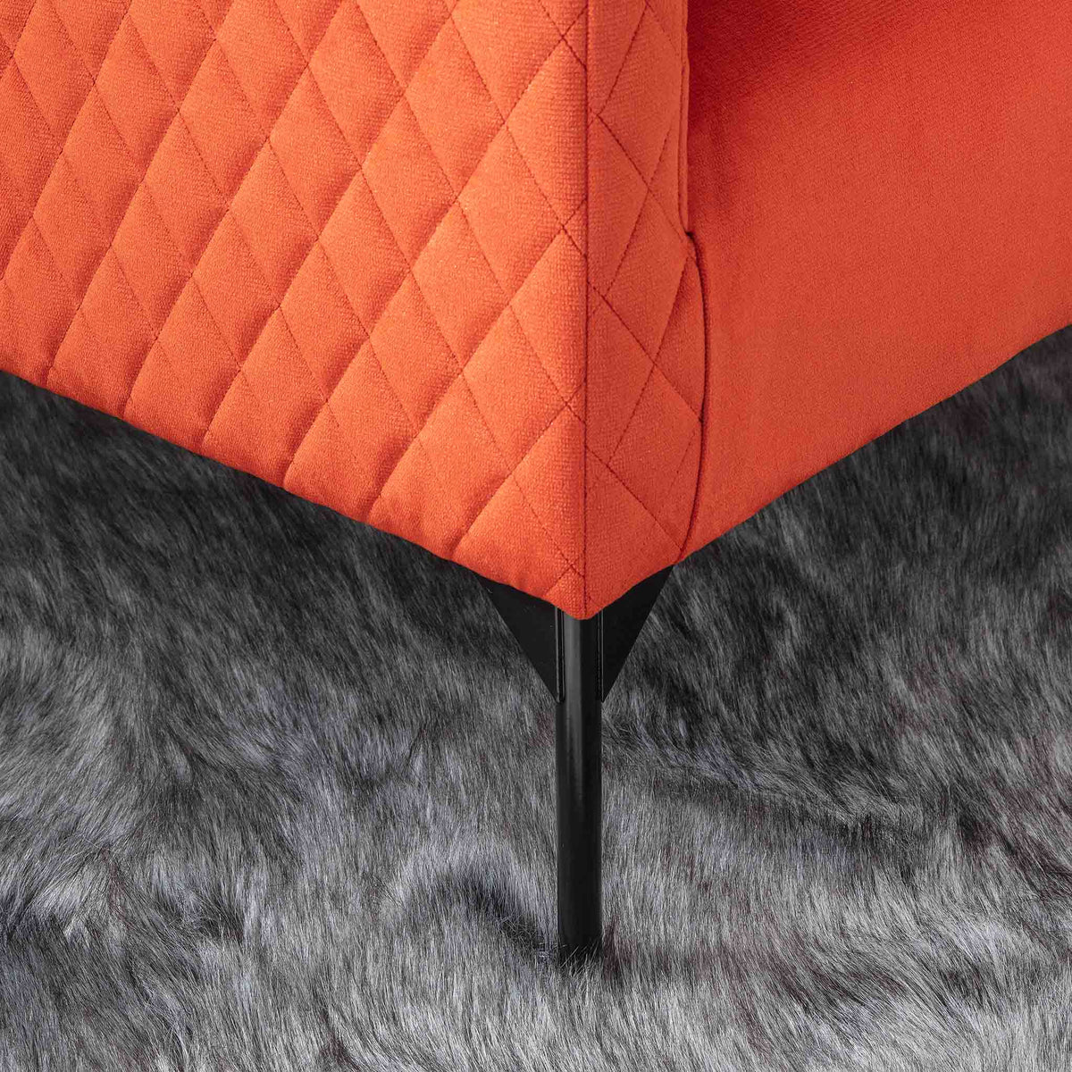 lifestyle close up of the black legs on the Bali Apricot Velvet Accent Chair
