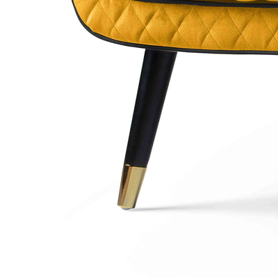 close up of the black leg with gold tipped feet on the Monty Gold Two Seater Chair