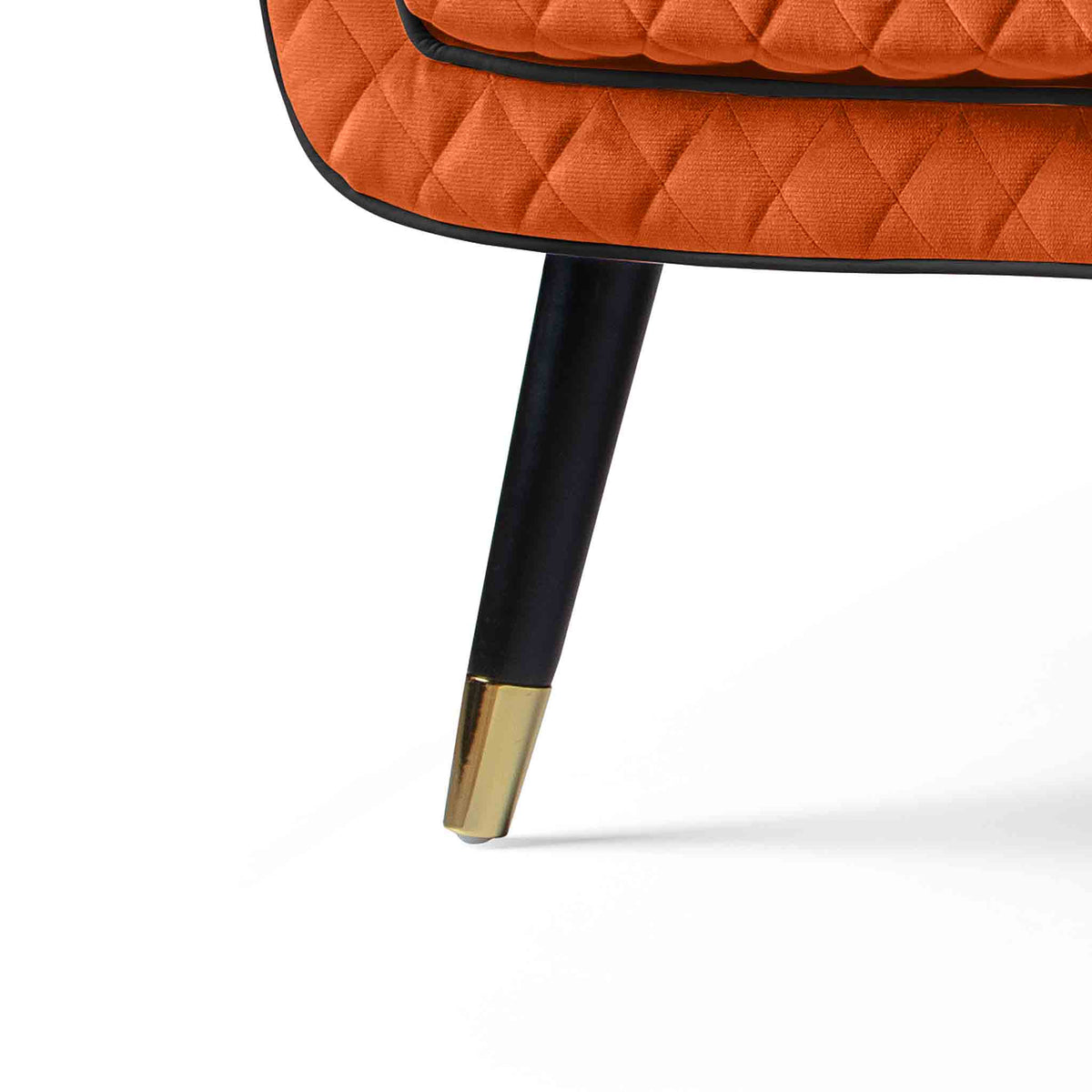 close up of the black legs with gold tipped feet on the Monty Apricot Two Seater Chair
