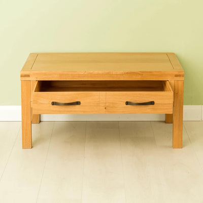 The Abbey Waxed Oak Coffee Table with Storage - Lifestyle front view with drawer open