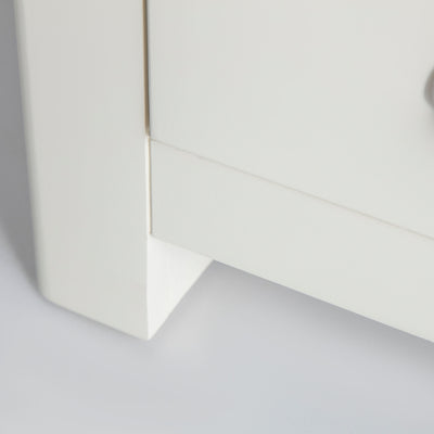 Close up of white painted wooden legs on The Padstow White Wooden Bedside Table with 3 Drawers