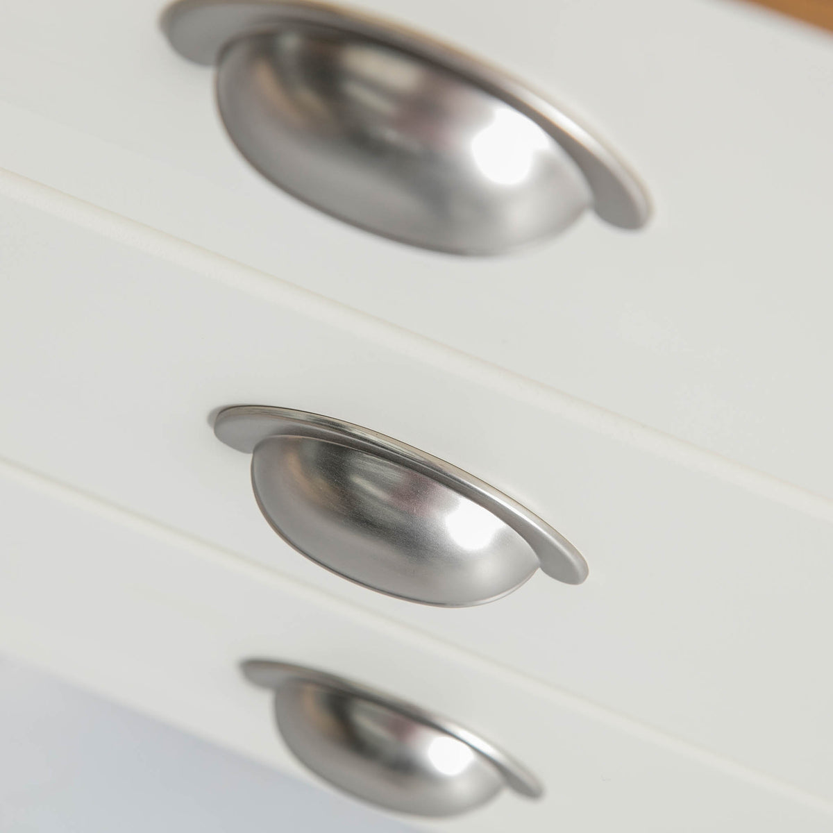 Close up of the metal cup handles on The Padstow White Wooden Bedside Table with 3 Drawers