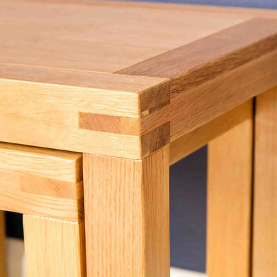 Close up corner joint of the Abbey Light Oak Nest of 2 Square Tables by Roseland Furniture