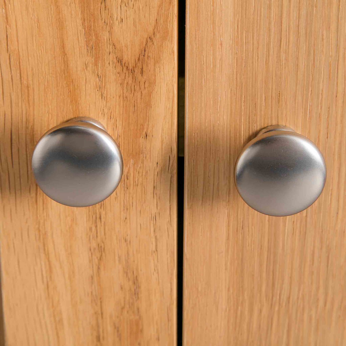 close up of metal round door knobs on the London Oak Mini Sideboard by Roseland Furniture.