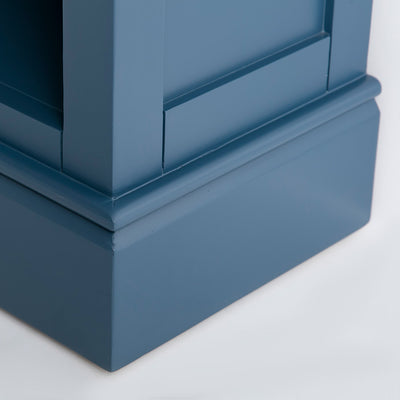 Side view of the painted blue wooden plinth base on the Chichester Stiffkey Blue Grey Low Bookcase