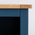 Close up of the oak top egde and blue painted frame on the Chichester Stiffkey Blue Grey Low Bookcase