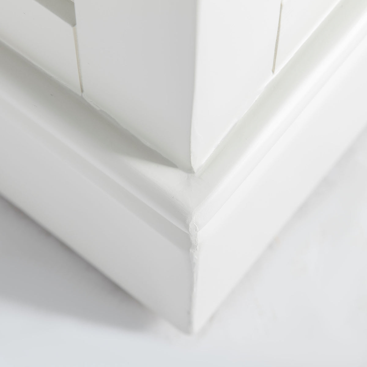 Close up of painted ivory plinth base on the Chichester Ivory Cream Mini Cupboard