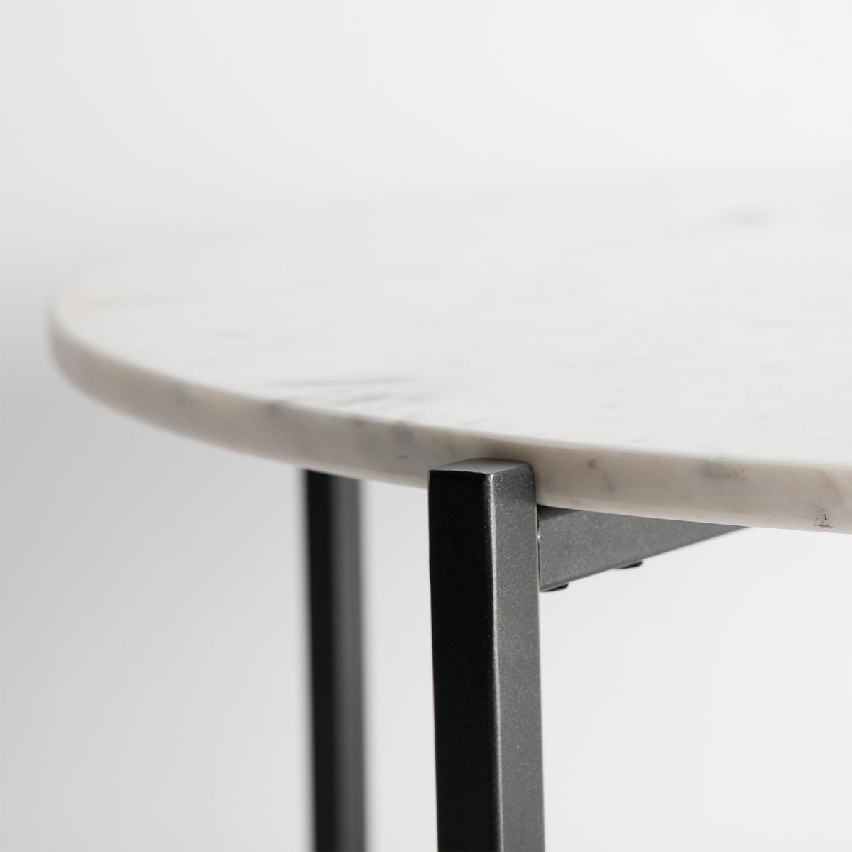 Close up of the round marble table edge on the Kandla White Round Marble Coffee Table with Grey Base