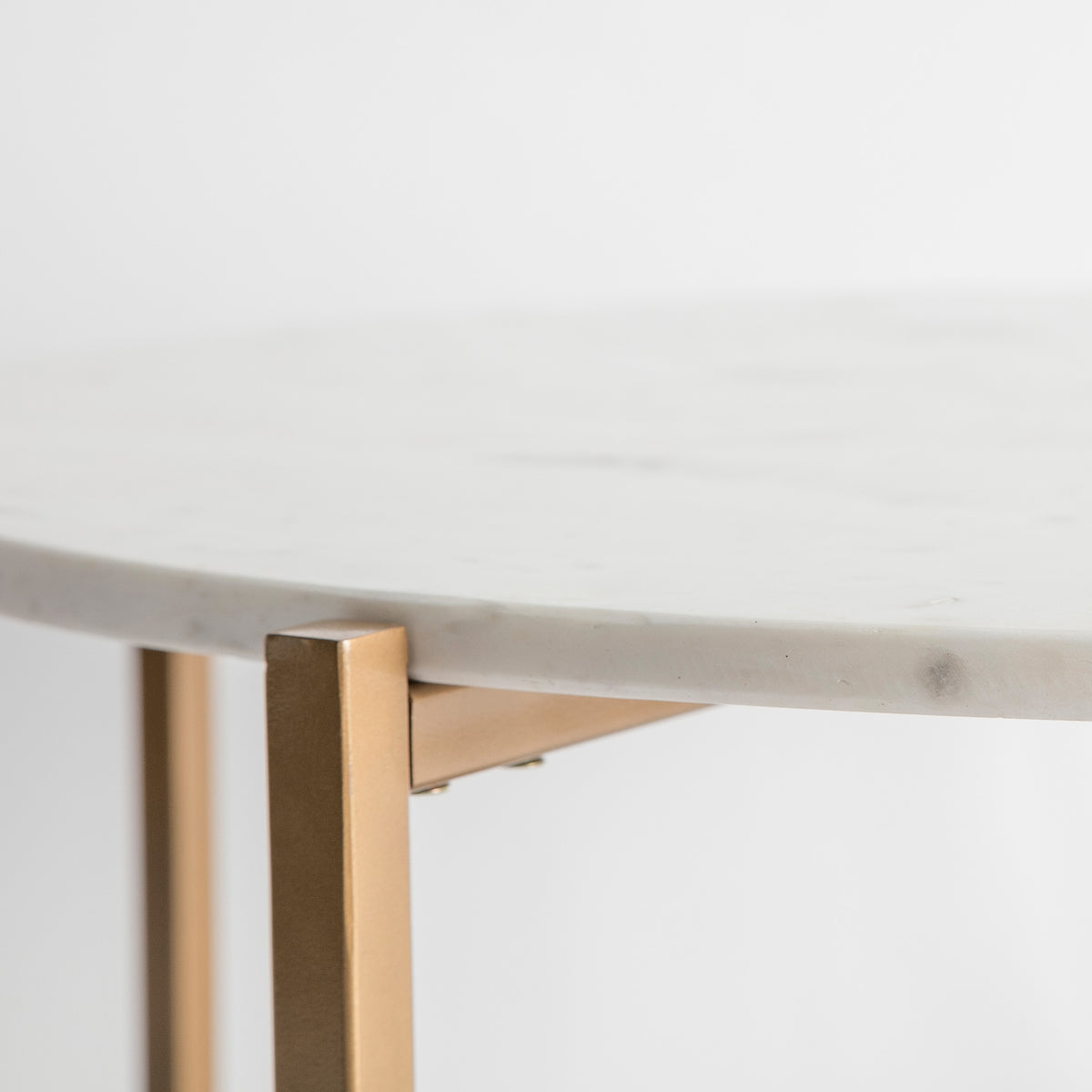Close up of the round marble edge on the Kandla White Round Marble Coffee Table with Gold Base