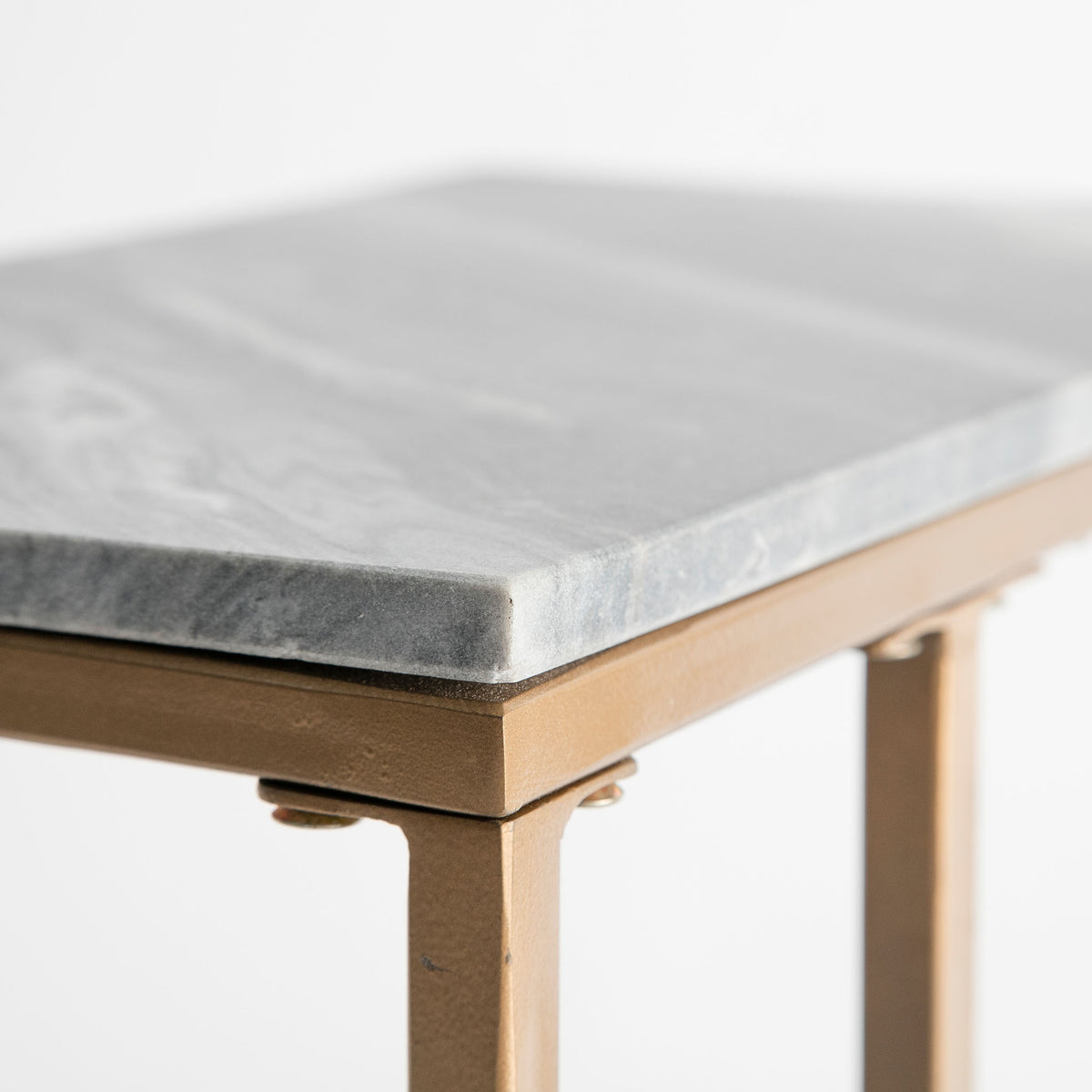 Close up of the light grey marble top edge on the Kandla Grey Marble Side Table with Gold Base