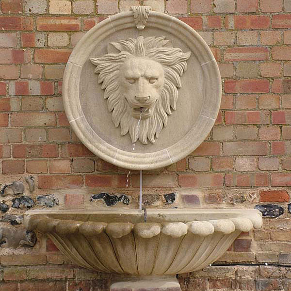 Lions head wall fountain in sandstone