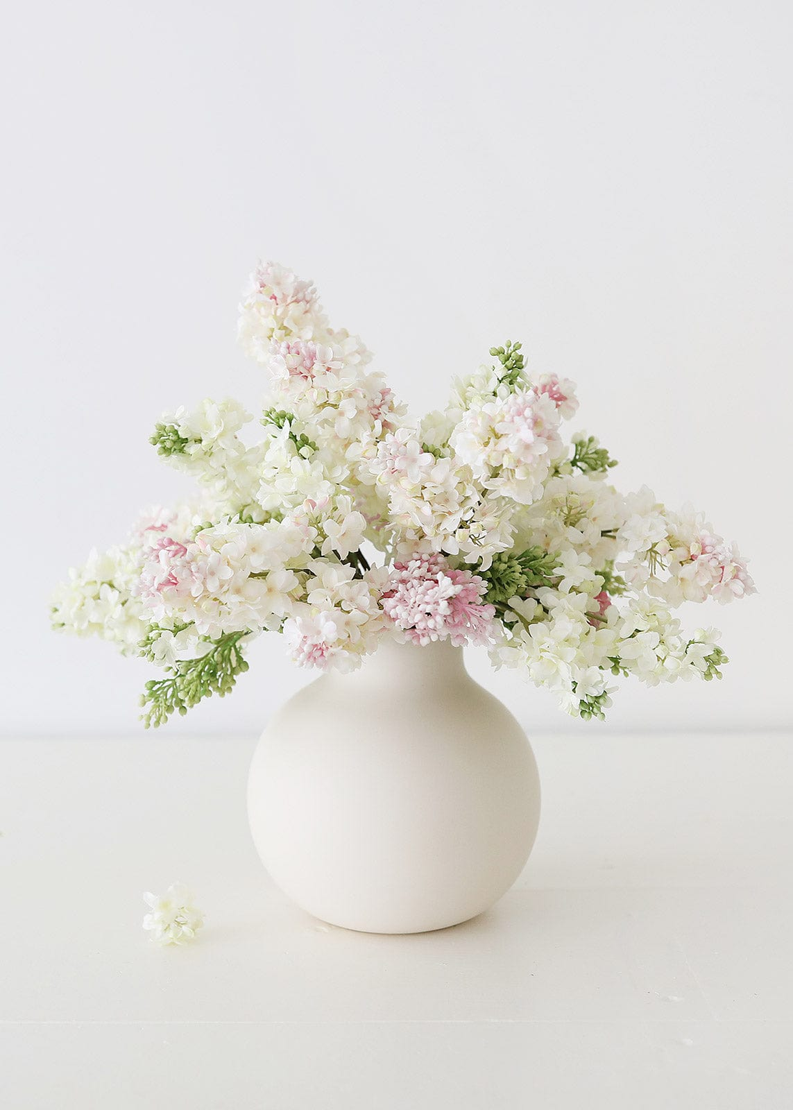 Cream and Pink Lilacs in White Round Vase