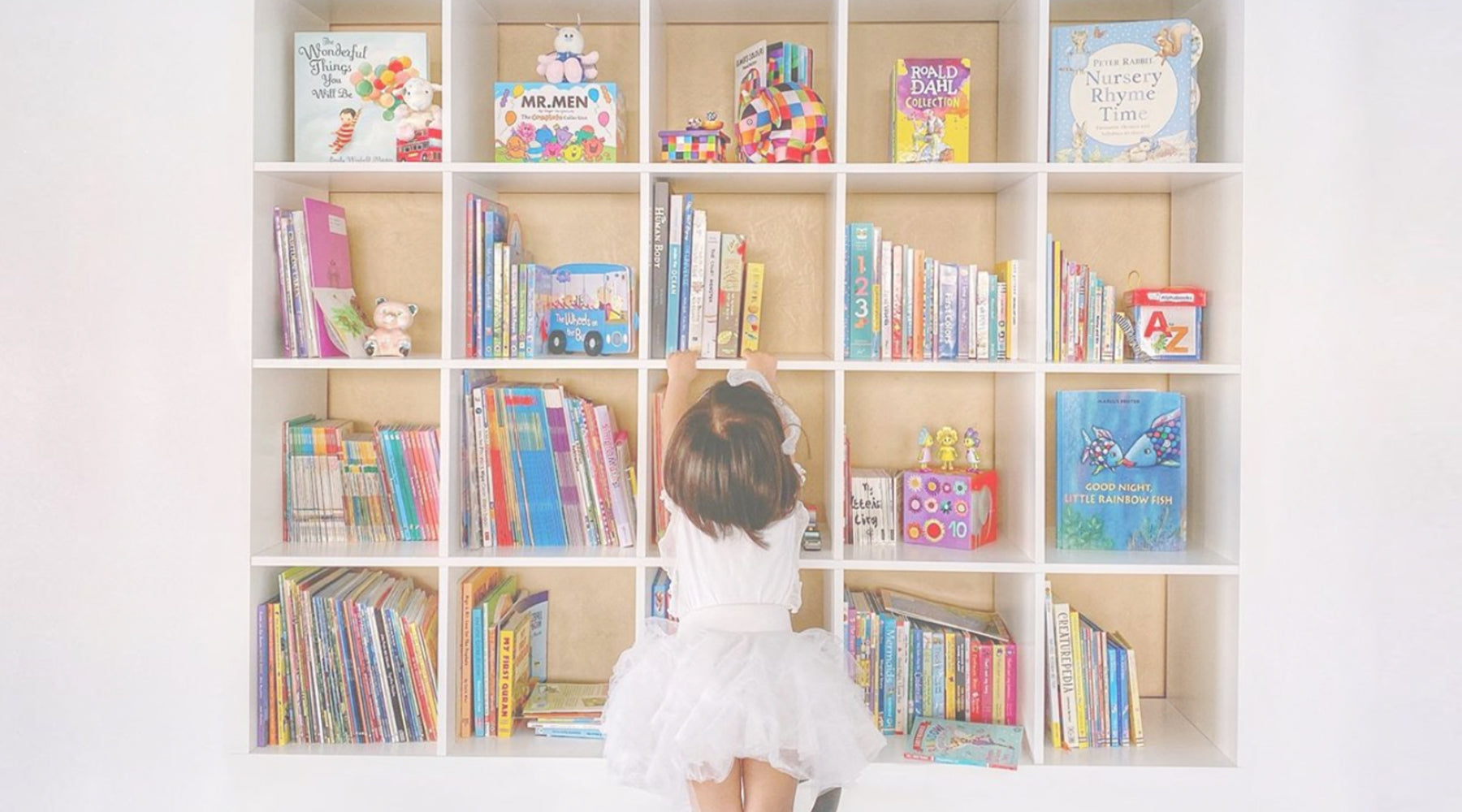 Little girl in white dress reaching for books in her bookshelf