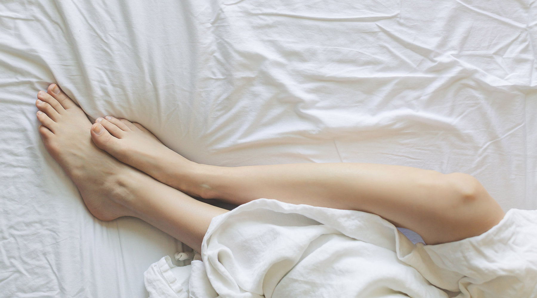 Legs in bed with white sheets