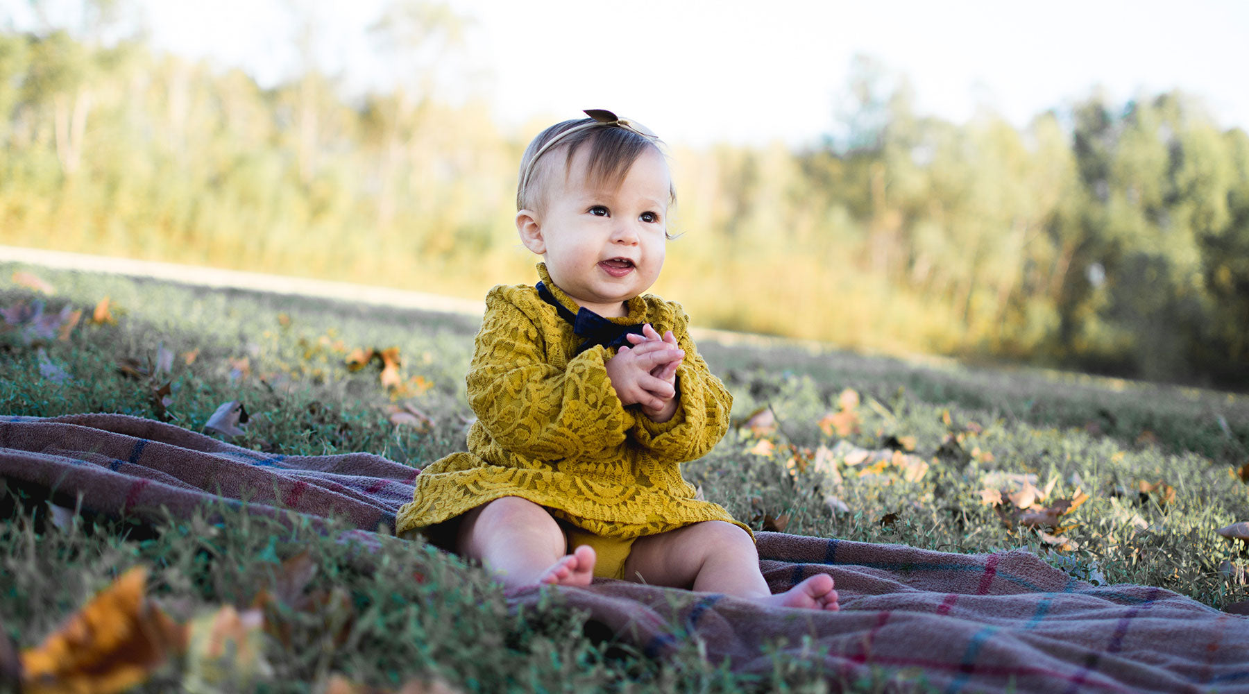 Baby girl sitting on a picnic blanket outdoors