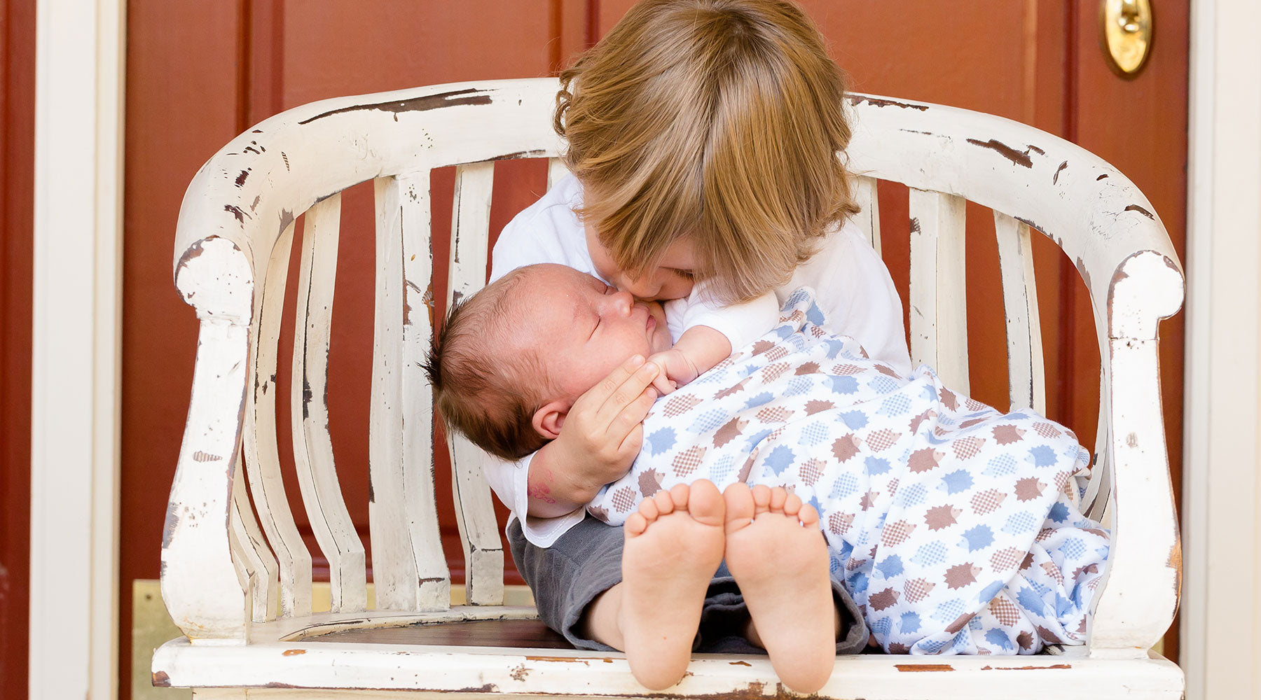 Older brother kissing newborn sibling