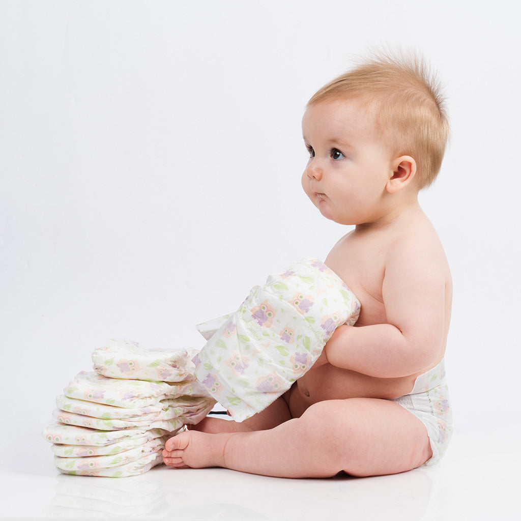 Cute baby holding Happy Little Camper diapers