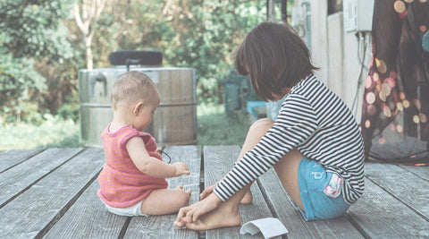 Older sister sitting on porch with baby toddler
