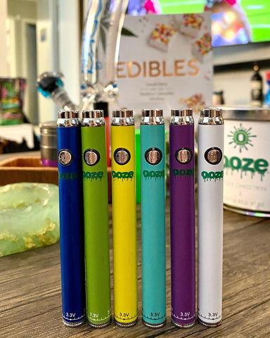 6 Ooze Slim Twist Batteries are lined up on a wood coffee table with other accessories visible in the background. From left to right the colors are blue, green, yellow, teal, purple, and white.