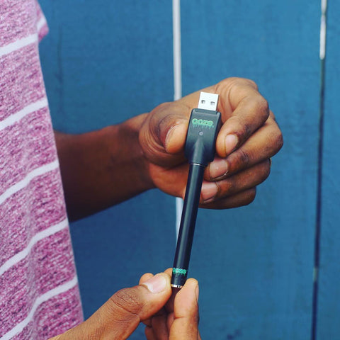 A black male wearing a red and white striped shirt holds a black Ooze touchless vape pen battery with the charger attached against a blue background.