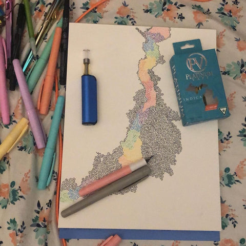 A blue Ooze Novex vaporizer battery is resting on a piece of art that is being colored in. It's laying on a bed with a blue Platinum Vape Cartridge box and a few colored pencils on top. There is a pile of markers and other colored pencils off to the left.