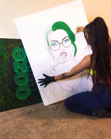 A young woman with long brown hair paints the green hair of a portrait of a girl on a canvas. She is wearing a black rubber glove, and there is a painting of the Ooze logo behind the canvas she is working on.