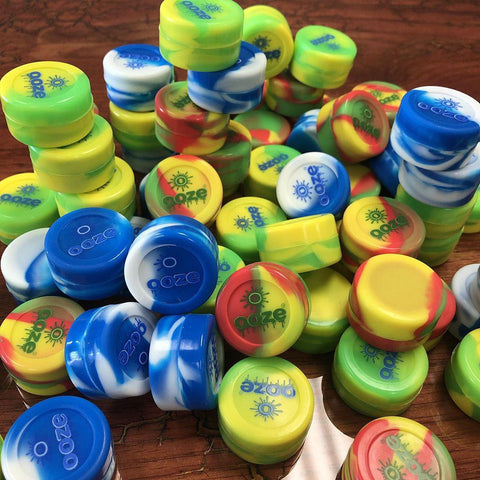 A huge pile of 5ml Ooze non-stick silicone concentrate containers sits on a wood table