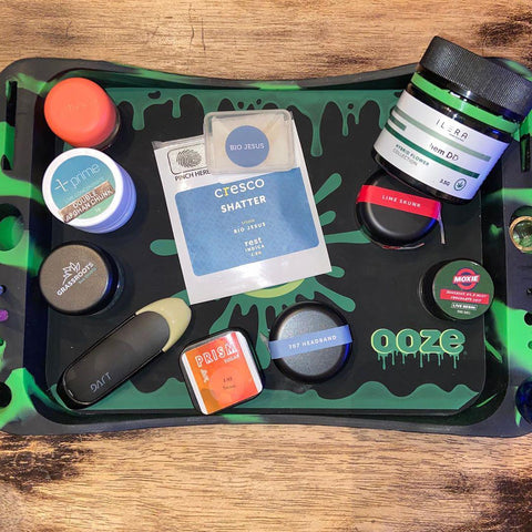 The Ooze Dab Depot storage tray sits on a wooden surface, and is filled with different cannabis products and tools.