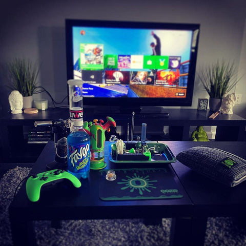 A shot of a living room from the couch. In front is a coffee table filled with different Ooze smoking products including the Rasta Trip and dab mat, and there is a tv with the Amazon FIre Stick home screen on in the background.