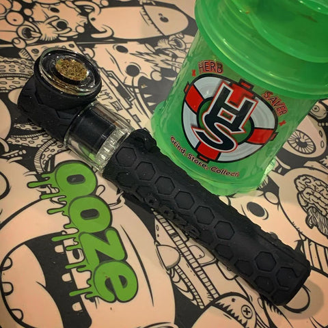 The black Ooze Piper is sitting on an Ooze biodegradable rolling tray with a green Herb saver grinder behind it. The bowl is fully packed with flower.