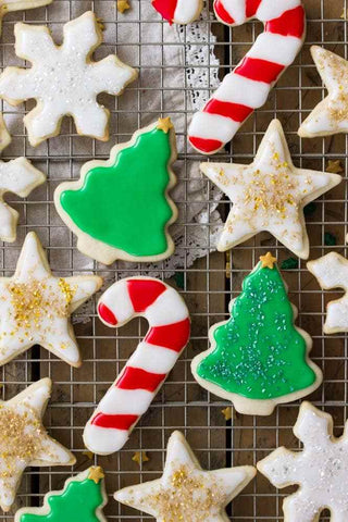 Photo credit to the Sugar Spun Run blog (https://sugarspunrun.com/easy-sugar-cookie-recipe/). A baking cooling rack is filled with finished Christmas sugar cookies that are decorated with frosting. There is a mix of Christmas trees, candy canes, gold stars, and white snowflake cookies