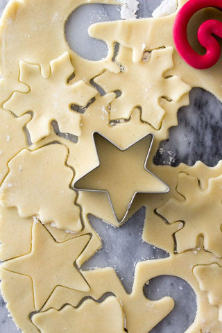 Photo credit to the Sugar Spun Run blog (https://sugarspunrun.com/easy-sugar-cookie-recipe/) An overhead shot of Christmas sugar cookie cutouts. The raw dough is being cut with a variety of cookie cutter shapes: snowflakes, stars and candy canes.