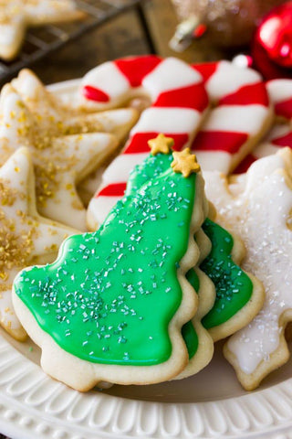 Photo credit to the Sugar Spun Run blog (https://sugarspunrun.com/easy-sugar-cookie-recipe/). A pile of Christmas sugar cookies are arranged on a plate. Front and center are green Christmas trees with gold stars on top, gold star cookies are off to the left, and candy cane cookies are in the back.