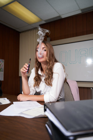 A young brunette woman is sitting at a desk with papers and binders scattered across. She is wearing a white blouse and smoking a black Ooze Quad vape pen battery. There is a cloud of smoke coming out of her mouth and covering some of her face.