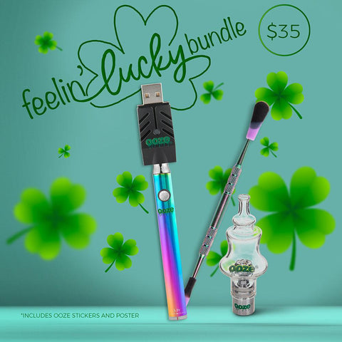 The Ooze Feelin' Lucky Bundle graphic has a teal background and four leaf clovers scattered around. The Rainbow Slim Twist vape battery is shown with the Smart USB charger attached. A rainbow dab tool and the Genie glass globe are to the right.