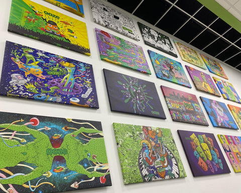 Designs of past Ooze rolling trays are printed on large canvases and hung on a white wall in the Ooze office.