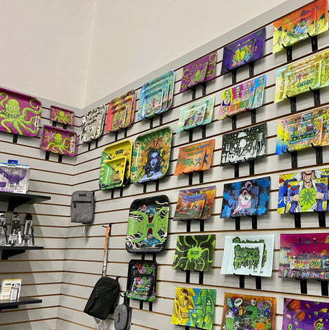 The rolling tray display wall in a corner of the Ooze Wholesale showroom. All the 2021 rolling tray designs are shown in the shatter-resistant glass rolling trays on a wall with light gray paneling. Black shelves can be seen on the left side of the photo with products displayed.