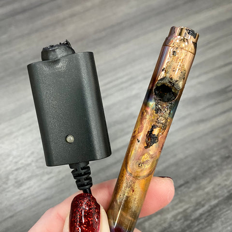 A rose gold Ooze Slim Twist Vape Battery has been burned and severely damaged from overheating due to use of a non-Ooze charger. The charger is also next to the battery, and the connector has been melted.