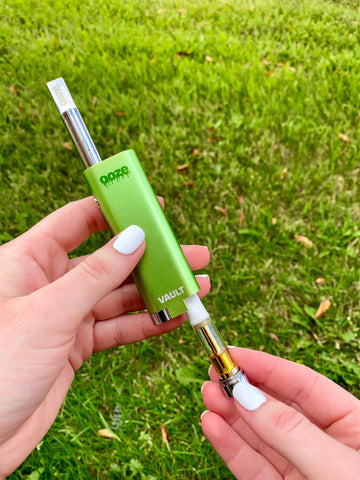 A white female holds the green Ooze Vault battery in both hands outside on a lawn. She holds the battery in her left hand, and is using her right hand to remove a cartridge stored in the hidden compartment.