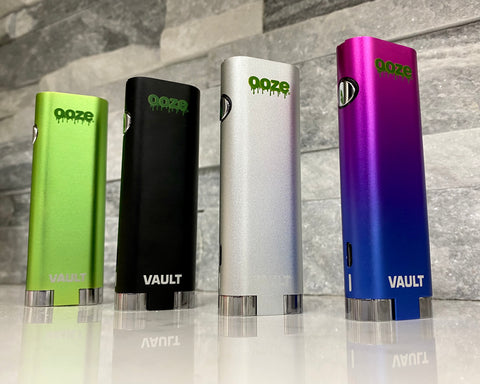 The four Ooze Vault batteries are lined up in a row on a white granite counter in front of a gray stone backsplash. From left to right the colors are green black, silver and rainbow.