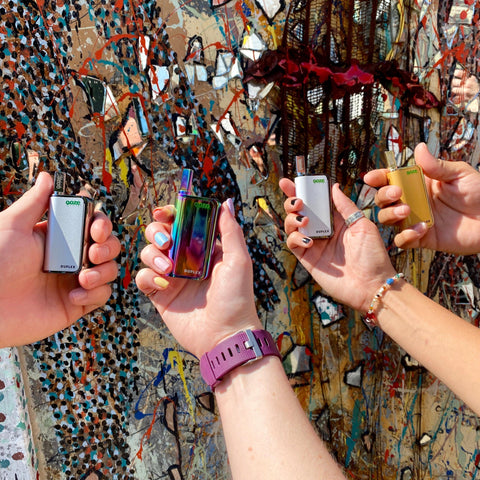 Four people are lined up in front of an abstract mural, with just one forearm of each showing. Each person is holding an Ooze Duplex Dual Extract Vaporizer. From left to right, the device colors are Chrome, Rainbow, White, and Gold.