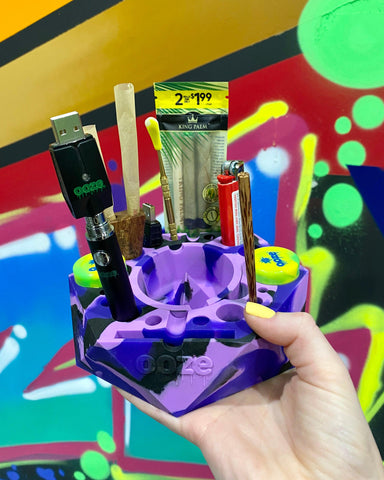 A white female holds the Mystic Ink Ooze Bangarang silicone ashtray and storage system in her hand in front of a graffiti wall. The tray is loaded up with tools, a battery, King Palm wraps and other accessories.