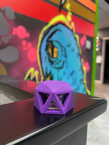 A purple Ooze Geode silicone glass concentrate stash jar is sitting on a black wood ledge in the Ooze break room. A graffiti wall with a blue monster is visible in the background.