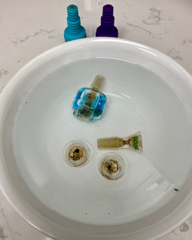 Four Ooze bowls are soaking in a white bowl filled with clear liquid to remove the debris. A blue Glyco bowl, regular Ooze flower bowl, and two Armor Bowl inserts are there, with the Armor Bowl silicone sitting on the counter.