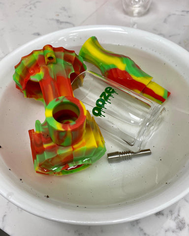 A Rasta Ooze Clobb hybrid water pipe is fully disassembled and soaking in a white bowl in a clear liquid to remove the debris. The bowl is on a white granite countertop.