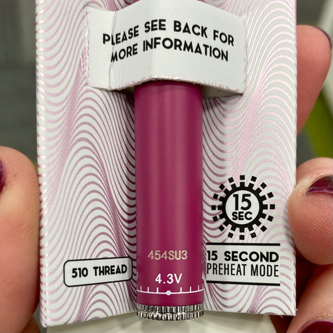 A close-up shot of a pink Ooze Slim Twist Vape Battery, in the original inner packaging. It is showing the warranty number on the bottom of the battery.