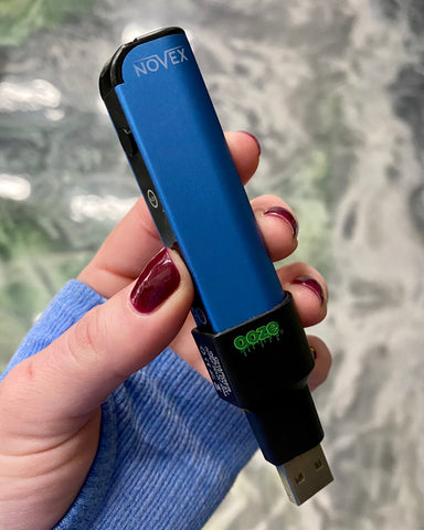 A white female hand holds a blue Ooze Novex vape battery in her hand, with the Magnetic Charger attached to show how it fits on the device.