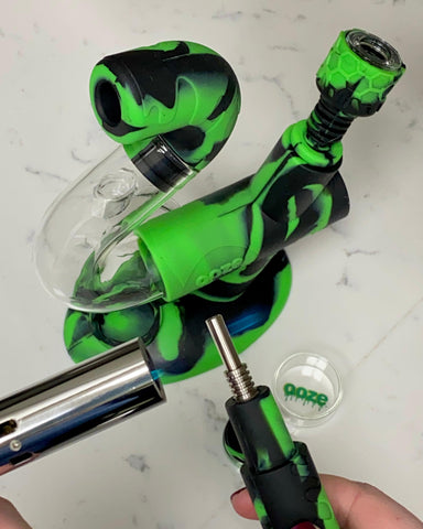 The mouthpiece of the Chameleon black and green Ooze Swerve silicone glass 4-in-1 hybrid piece has the titanium nail inserted to turn it into a nectar collector. The nail is being heated by a torch, and the body of the piece is directly behind it.