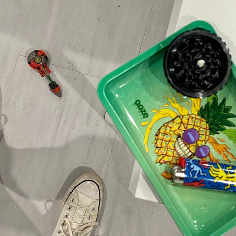 A shot looking down at the floor. The Ooze after midnight Bowser Travel Pipe is on the floor facing up with a fully packed bowl. A white converse sneaker is at the bottom of the frame. On the edge of the white table is a small metal Mr. Pineapple Ooze rolling tray, a black Saturn grinder bottom piece, and a blue K. Haring lighter.